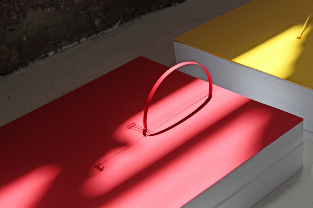 "Marco Maggi, ""Underline,"" 2014 (detail). Sixty 8 1/2 in. x 11 in. reams of paper; cuts and folds on 8 1/2 in. x 11in. sheets of yellow, blue, and red Wassau card-stock. Courtesy of Hosfelt Gallery."