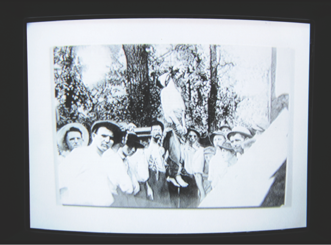 "Oliver Lutz, ""The Lynching of Leo Frank,"" 2009 (2010 SFMOMA installation view); Acrylic on canvas, CCTV system; painting: 60 x 87 in. (152.4 x 221 cm) overall dimensions variable. Courtesy the artist; photo: Ian Reeves, courtesy SFMOMA; © Oliver Lutz."