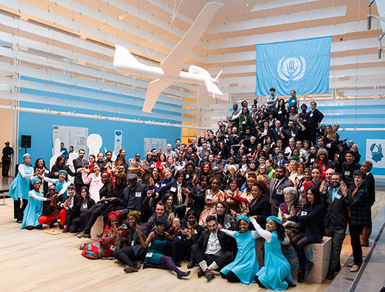 "Citizen-delegates and other participants of The People's United Nations (pUN), Drone Dove in foreground and official pUN flag with motto ""Hands-on with a vision"" in background. Queens Museum, New York City, 2013. Courtesy of the artist."