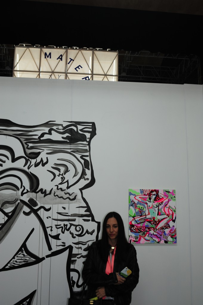 Mira Dancy infront of her work at Night Gallery, with the latin word for mother behind her.