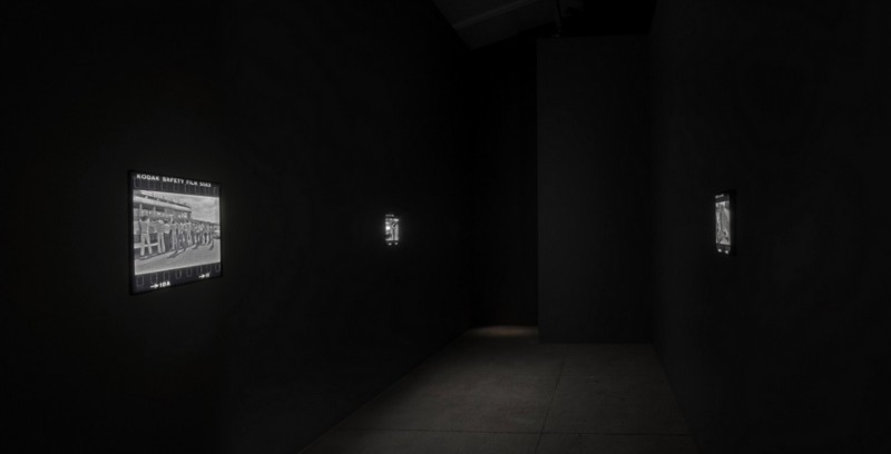 """Alfredo Jaar. """"Shadows."""" Installation View, lightboxes with black and white transparencies, 12 x 13 inches each. Original photograph by Koen Wessing (1942-2011): Estelí, Nicaragua, September 1978. Courtesy: Galerie Lelong, New York; © Netherlands Fotomuseum, Rotterdam, 2015."""