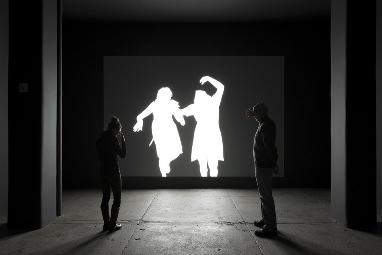 "Alfredo Jaar. ""Shadows."" Installation View, installation with LED lights, aluminum, video projection, 116 x 174 inches. Original photograph by Koen Wessing (1942-2011): Estelí, Nicaragua, September 1978. Courtesy: Galerie Lelong, New York; © Netherlands Fotomuseum, Rotterdam, 2015."