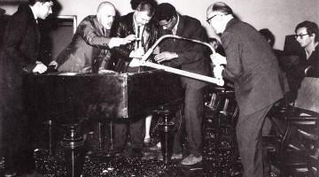 George Maciunas, Dick Higgins, Wolf Vostell, Benjamin Patterson & Emmett Williams performing Philip Corner's Piano Activities at Fluxus Internationale Festspiele Neuester Musik, Weisbaden, 1962. Photograph by Hartmut Rekort. Courtesy of the Internet.