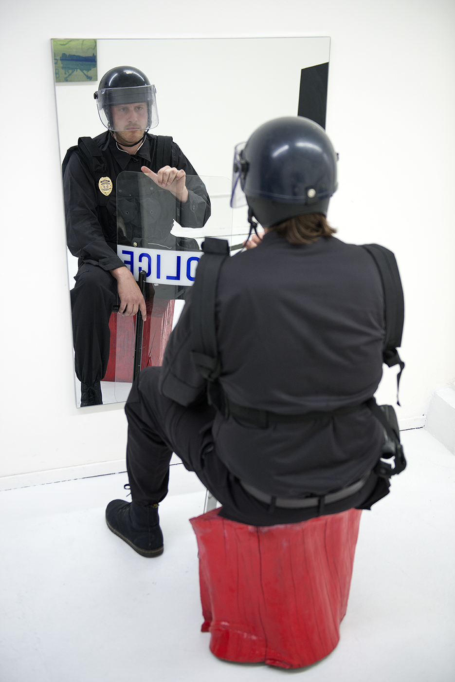 "James Cordas, ""Contemplative Cop (8ft. Cop)"", 2015. Dimensions variable. Actor, red tree stump, tactical crowd suppression equipment, mirror. Image courtesy of et al. gallery and the artist."