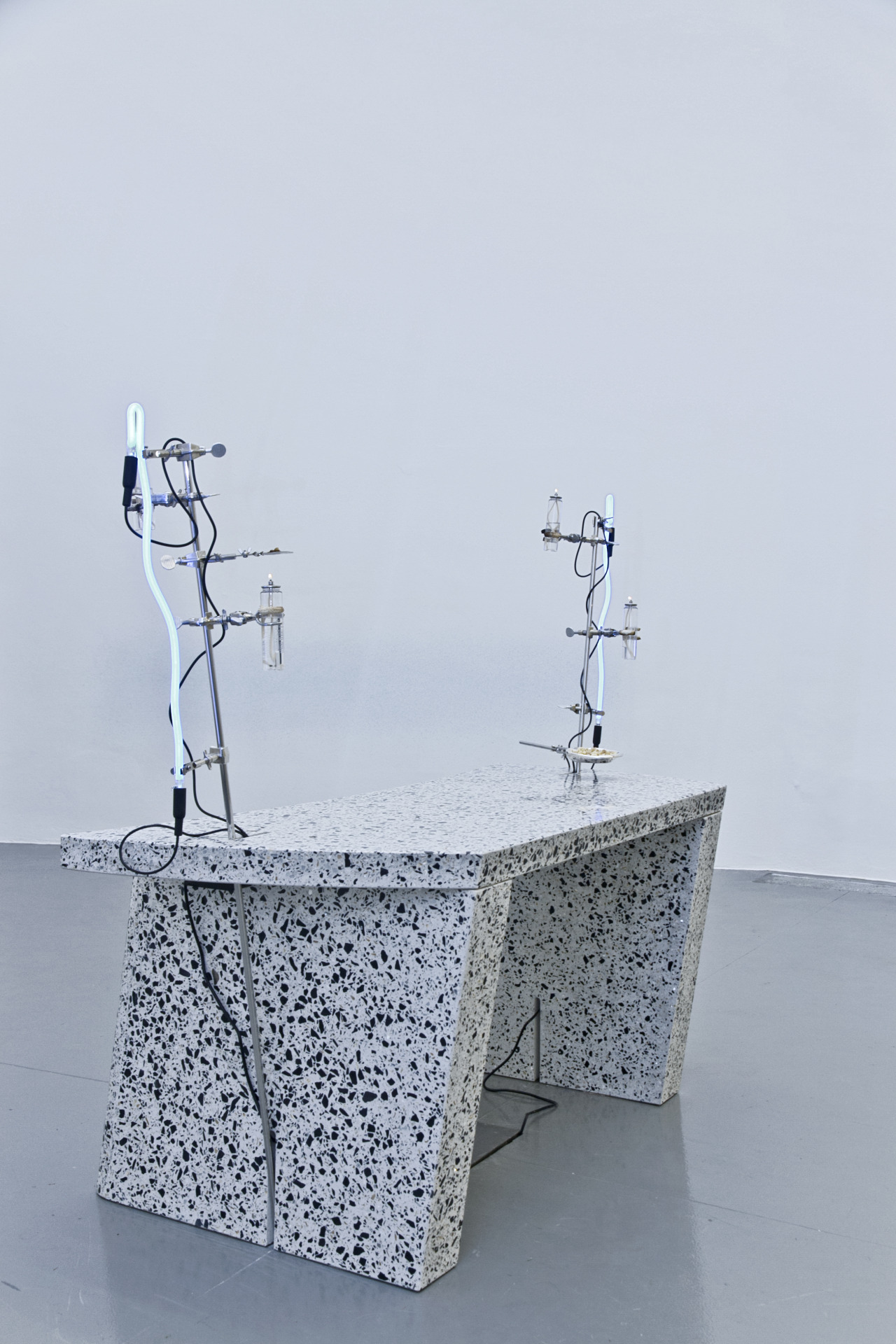 A day dream about the authority of a heavy desk, about other vocations spent behind one ordering certain men around, about domineering and maybe reclining slowly, exhaling, 2014. Terrazzo, stainless steel, laboratory hardware, neon lights, transformers, paraffin lamps, mica, frankincense, sterling silver Tiffany dish. Variable dimensions. Courtesy of the artist.