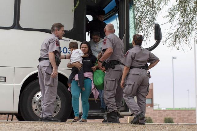 Migrants, consisting of mostly women and children, disembark from a U.S. Immigration and Customs Enforcement (ICE) bus at a Greyhound bus station in Phoenix, Arizona May 29, 2014. Photograph by Samantha Sais.