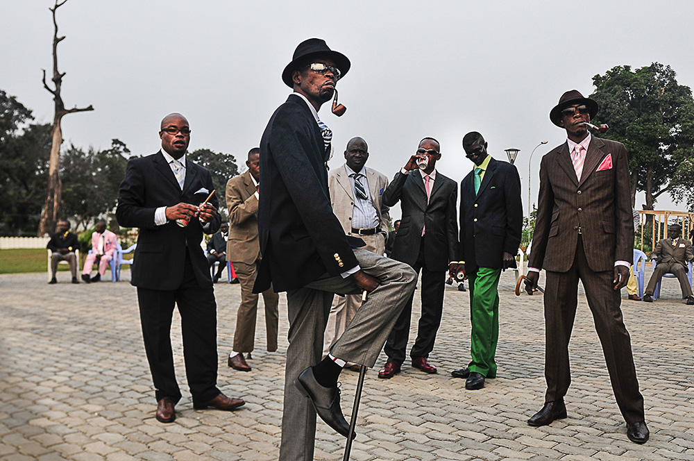 "Daniele Tamagni. ""Sapeurs posing in front of Memorial Savorgnan de Brazz, Brazzaville,"" 2008. Digital print. 25.9 x 35.8 in"
