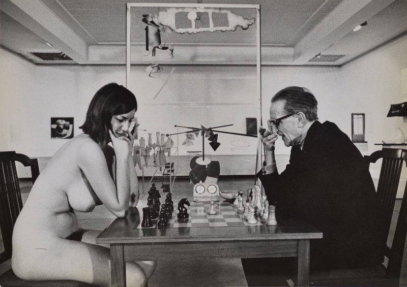 "Julian Wasser. ""Chess Match, Duchamp scratching nose,"" Duchamp Retrospective, Pasadena Art Museum, 1963 vintage gelatin silver print. 6.75 x 9.5"". Courtesy Robert Berman Gallery."