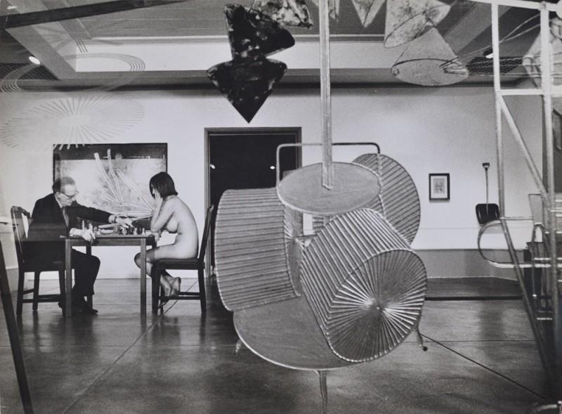 "Julian Wasser. ""Duchamp making a chess move in distance, Duchamp Retrospective, Pasadena Art Museum, 1963."" Vintage gelatin silver print. 10 x 13.5"" courtesy Robert Berman/E6 Gallery."