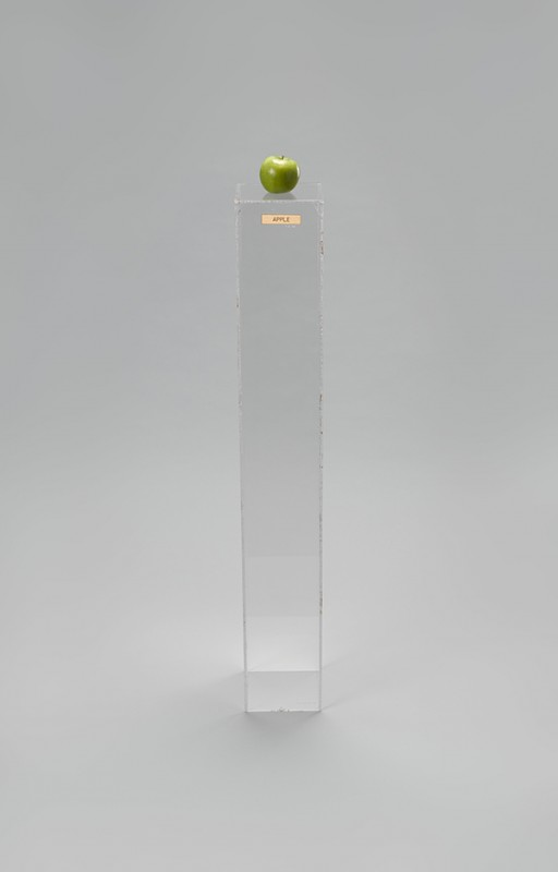 "Yoko Ono (Japanese, born 1933). ""Apple,"" 1966. Plexiglas pedestal, brass plaque, apple, 45 × 6 11/16 × 6 15/16″ (114.3 × 17 × 17.6 cm). Private collection. © Yoko Ono 2014"