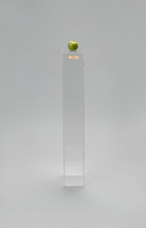 "Yoko Ono (Japanese, born 1933). ""Apple,"" 1966. Plexiglas pedestal, brass plaque, apple, 45 × 6 11/16 × 6 15/16″ (114.3 × 17 × 17.6 cm). Private collection. © Yoko Ono 2014"