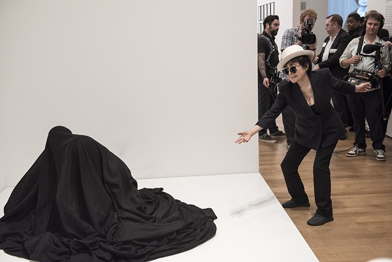 "Yoko Ono interacting with people activating Bag Piece (1964), a participatory work in ""Yoko Ono: One Woman Show, 1960-1971,"" on view at MoMA, May 17 -September 7, 2015. Photo by Ryan Muir © Yoko Ono"