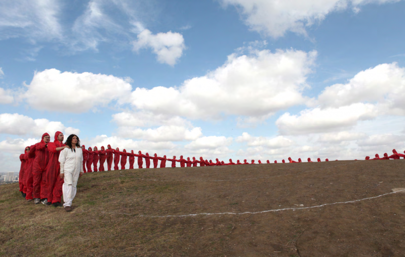 An Elongated Now, 2014. Documentation of performance for the Laguna Museum of Art, Art and Nature Festival. 300 performers dressed in white parallel the arc of Main Beach, Laguna over 3⁄4 of a mile. Laguna Beach, California. Photograph by Eric Minh Swenson. Courtesy of the artist and Kohn Gallery.