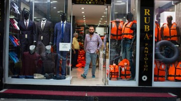 "A men's shop in Izmir, Turkey, has begun selling life jackets, capitalizing on a bustling ""raft economy"" that caters to an influx of migrants from the Middle East. Photograph by Tyler Hicks/The New York Times."