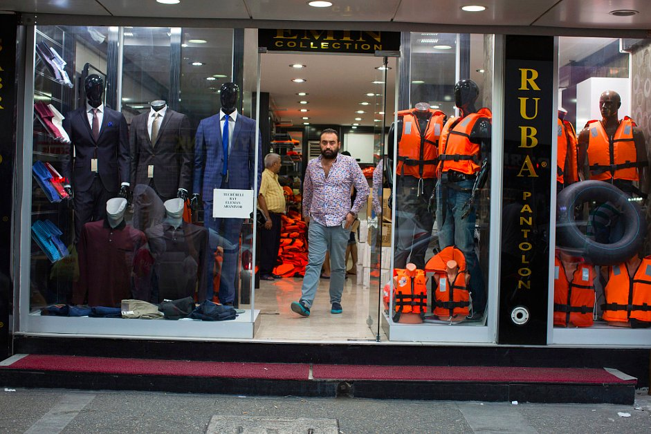 """A men's shop in Izmir, Turkey, has begun selling life jackets, capitalizing on a bustling """"raft economy"""" that caters to an influx of migrants from the Middle East. Photograph by Tyler Hicks/The New York Times."""