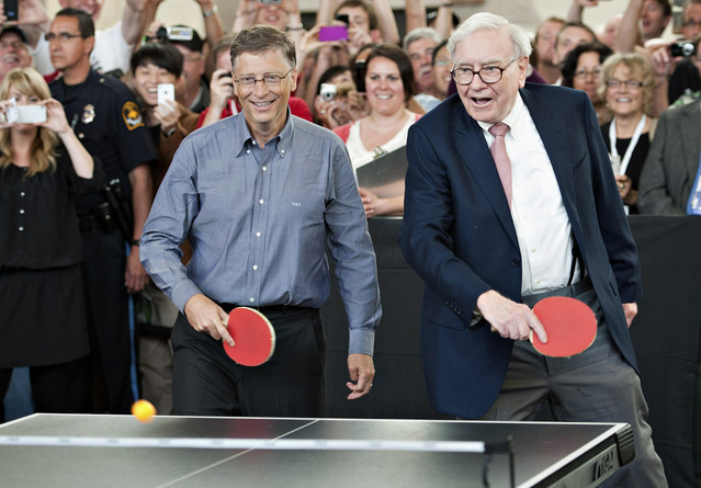 Warren Buffett and Bill Gates play table tennis Olympian Ariel Hsing during Berkshire Hathaway's annual shareholder meeting at Borsheims in Omaha, Nebraska on Sunday, May 6, 2012.