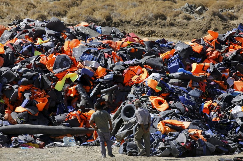 Locals survey a huge pile of deflated dinghies, tubes and life vests left by arriving refugees and migrants on the Greek island of Lesbos on Sept. 18, 2015. Photograph by Yannis Behrakis/Reuters.
