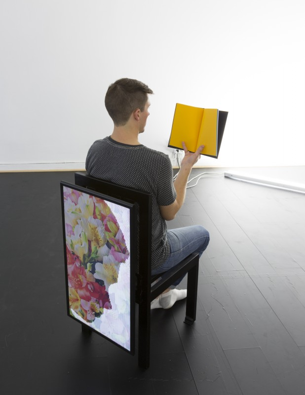 James Cordas, Chair, 2015. Brushed steel, LED monitor, book, James Gendron, perforated vinyl chair, 36 x 23 x 17 in.; human, 5 ft. 11 in. Image courtesy of the artists and City Limits. Photo: Kristine Eudy