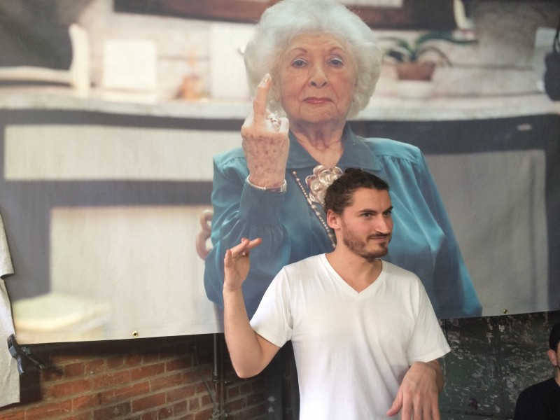 Ethan Rafal at Rob Pruitt's Flea Market, standing in front of an image of his grandmother.