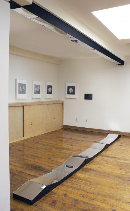 "Theodora Varnay Jones, Narcissus, 2016. Site specific installation, mirrored plexiglass, wood, floor 12"" x 14' X 5"", ceiling beam 5.5"" x 14' X 5.5"""