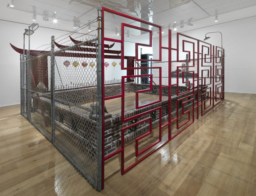 """Framed and Frame (Miniature Reproduction """"Chinatown Wishing Well"""" built by Mike Kelley after """"Miniature Reproduction 'Seven Star Cavern' Built by Prof. H.K. Lu"""") (""""Frame"""" section), 1999. 2 parts: steel cyclone fencing, wood, electrical fixtures, paper lanterns, faux concrete, wood, paper pulp, acrylic, statuary, spray paint, mattress, afghan, pillow, Vaseline, and condoms. """"Framed"""" section: 113 x 191 x 161 inches. """"Frame"""" section: 137 x 226 x 209 inches. Installation view, Framed and Frame at Hauser & Wirth London, 2016. © Mike Kelley Foundation for the Arts. All Rights Reserved / Licensed by VAGA, New York, NY. Collection of Rennie Collection, Vancouver. Courtesy of the Mike Kelley Foundation and Hauser & Wirth."""