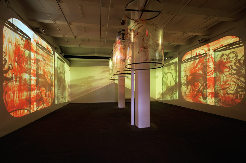 Nalini Malani, In Search of Vanished Blood, 2012, six-channel video (color, sound; 11:00 minutes) and five Mylar cylinders.  Installation view, Nalini Malani: In Search of Vanished Blood, Galerie Lelong, New York, 2013. Courtesy Galerie Lelong, New York and Paris. © 2016 Nalini Malani