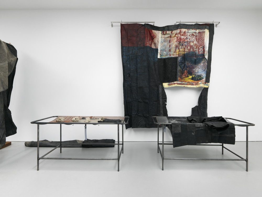 a futile mercantile disposition, 2016. Oil and oil stick on canvas and linen, stainless steel, vinyl, latex, copper, PVC tubing, self-hardening clay with ground corn, and single channel video, dimensions vary with installation. Courtesy of David Zwirner.