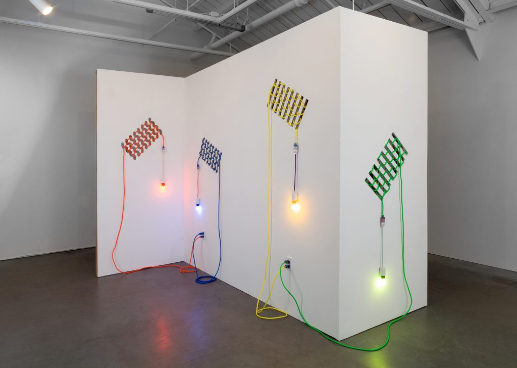 Dana Hemenway. Untitled (Drywall Weave), 2016; Laser cut drywall, wood, extension cords, custom fixtures, colored compact fluorescent light bulbs; 96 x 108 x 84 inches. Courtesy of the artist and Eleanor Harwood Gallery, San Francisco.