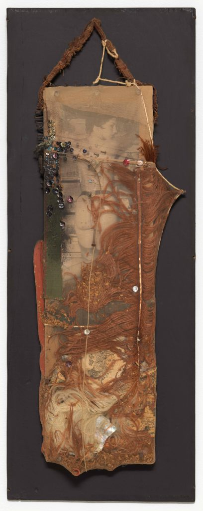BLACK DAHLIA, 1960; cut and pasted printed papers, feather, fabric, rubber tubing, razor blade, nails, tobacco, sequins, string, shell, and paint encased in nylon stocking over wood; 26 3/4 × 10 3/4 × 2 3/4 in. (68 × 27.3 × 7 cm); the Museum of Modern Art, New York, purchase; © 2016 Conner Family Trust, San Francisco / Artists Rights Society (ARS), New York